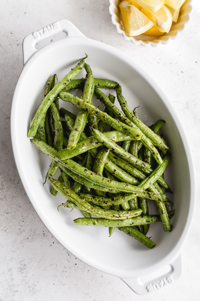 Overhead view of air fryer green beans in a white oval dish.