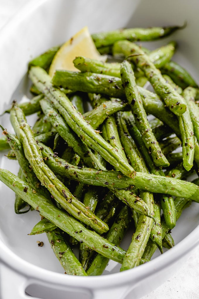 Up close view of air fried green beans in a white dish.