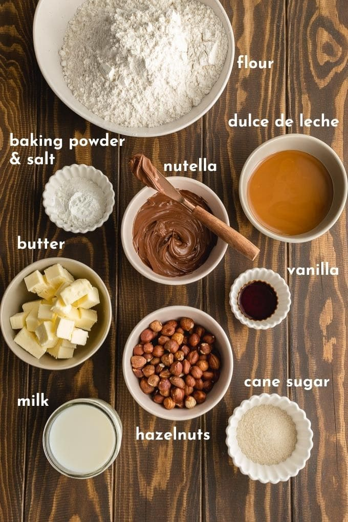 Ingredients to make Nutella buns labelled and arranged on a wooden surface.