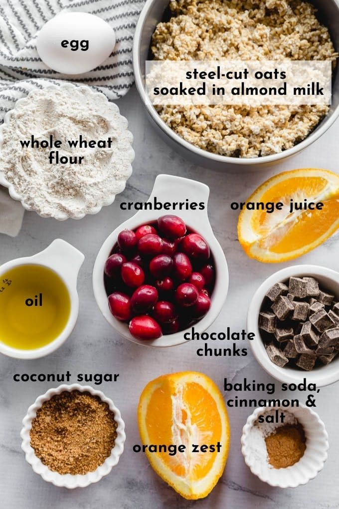 Ingredients to make cranberry orange muffins arranged on a work surface and labelled.