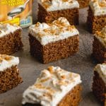 Easy Gingerbread Cake cut into squares and arranged on a grey surface.