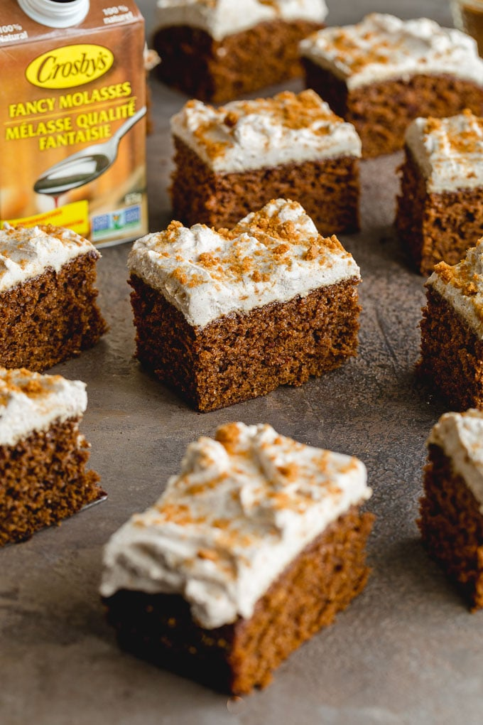 Pieces of gingerbread cake topped with dairy-free whipped cream with a carton of molasses in the background.