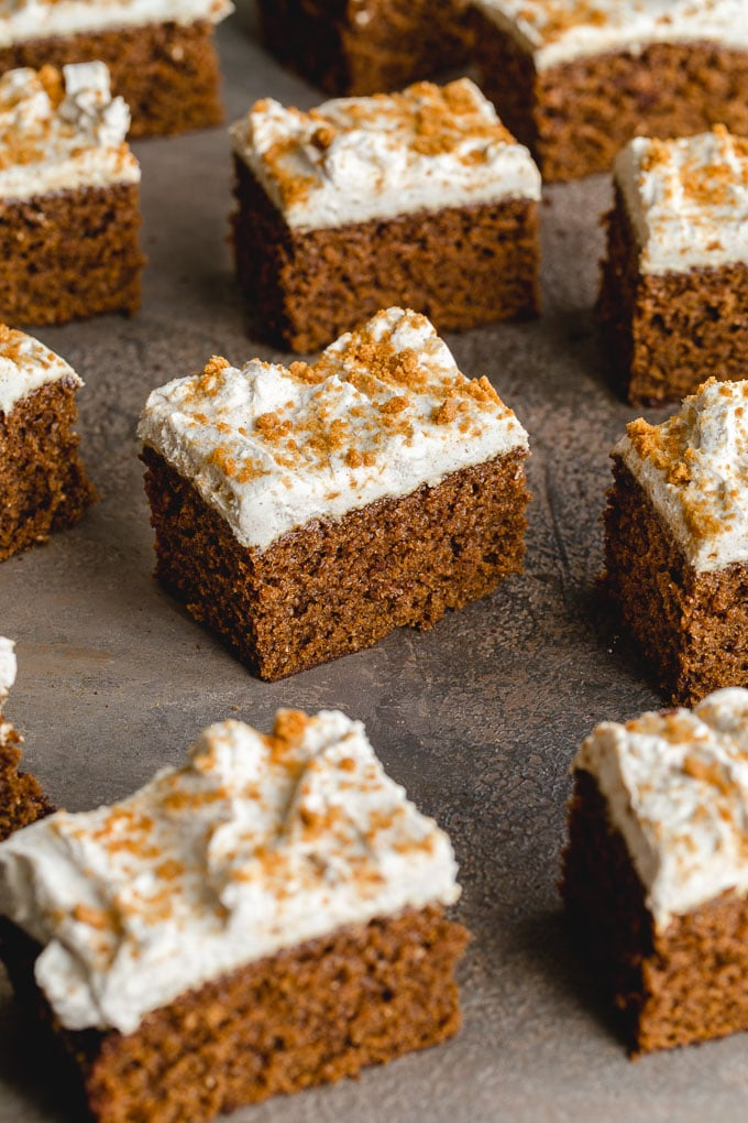 Up close view of pieces of gingerbread cake on a grey surface.
