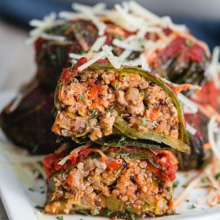 Stuffed Collard Greens cut in half and arranged on top of each other on a small plate.