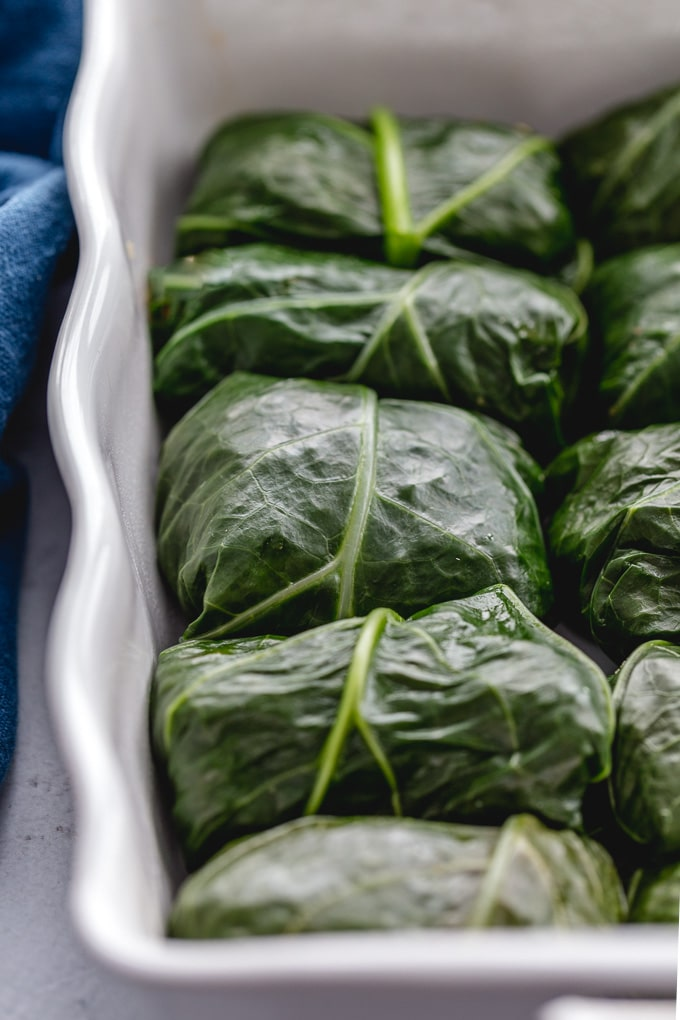 Up close view of collard green rolls arranged in a baking dish.