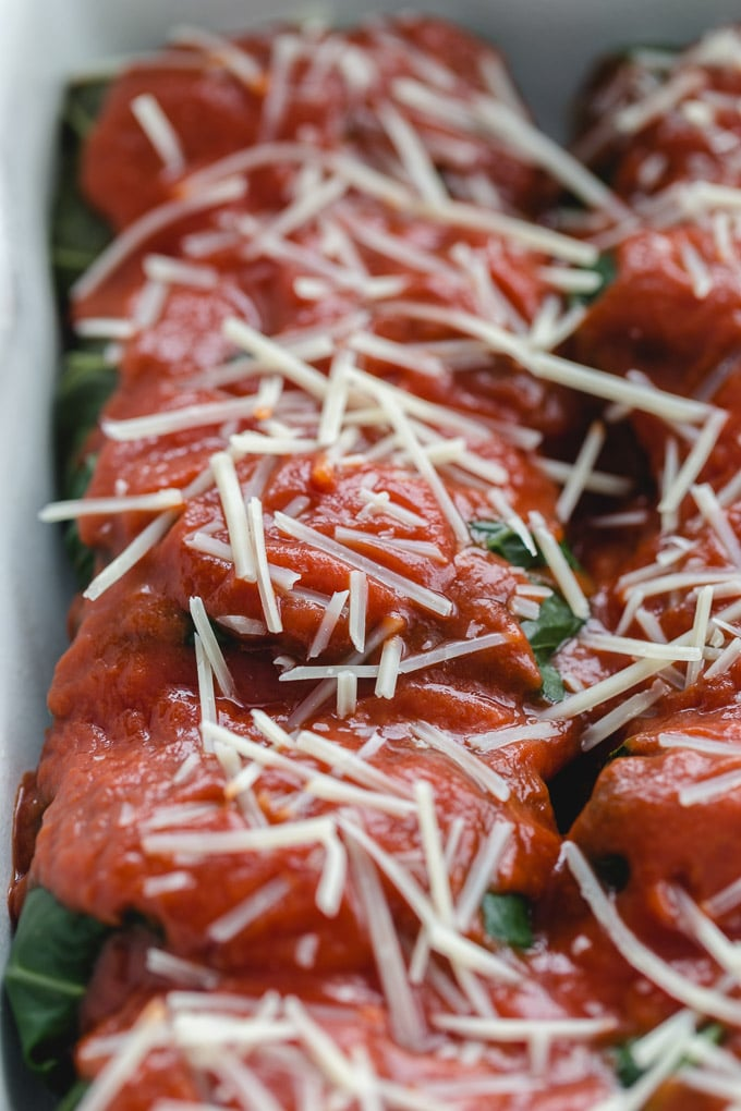 Up close view of collard green rolls topped with tomato sauce and parmesan cheese.