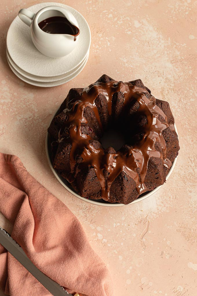 Cranberry bundt cake on a plate with chocolate poured over it and a pink napkin off to the side.