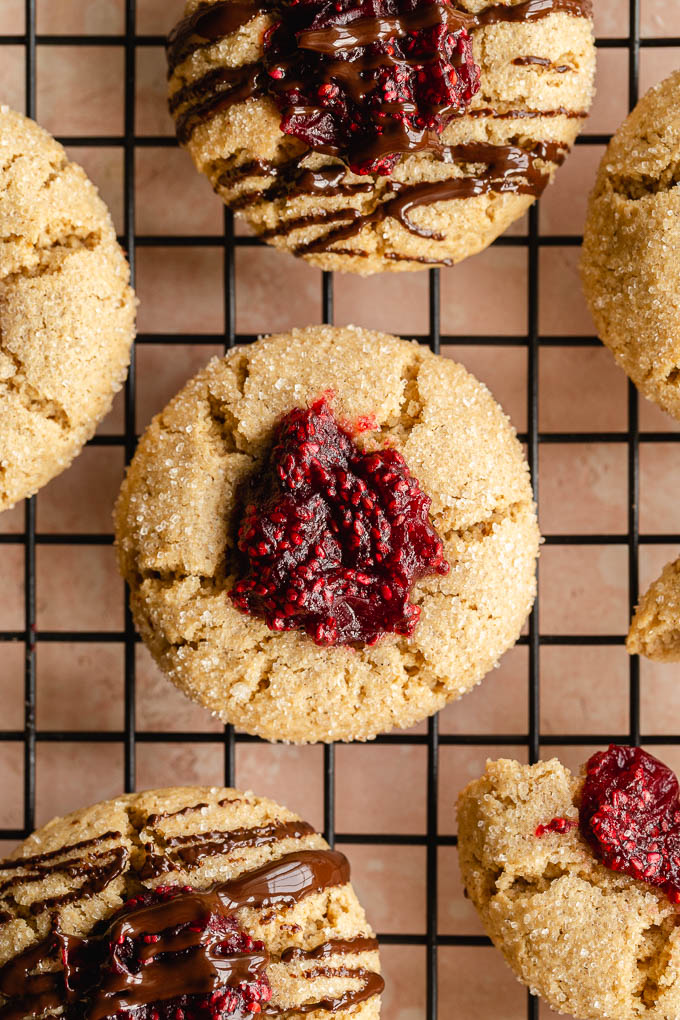Up close view of cranberry thumbprint cookies on a wire rack.