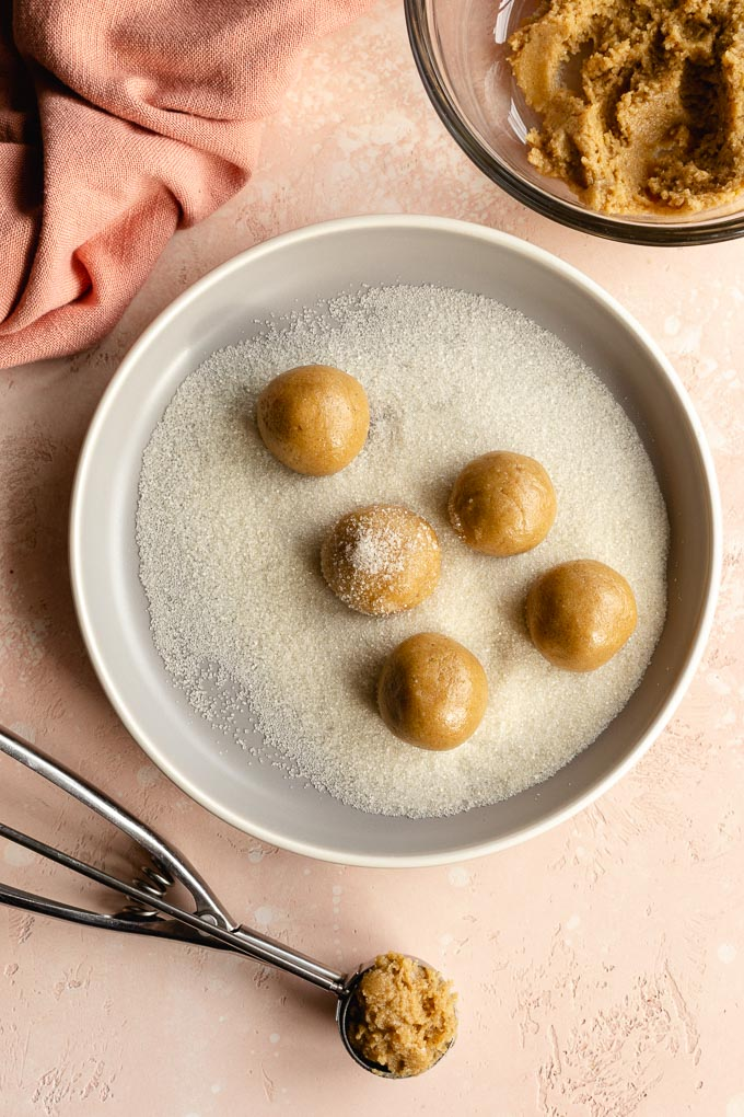 Thumbprint cookie dough being shaped into balls and rolled in sugar on a plate.