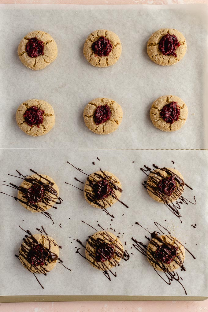 Gluten-free thumbprint cookies baked up on a cookie sheet, filled with cranberry jam and drizzled with melted chocolate.