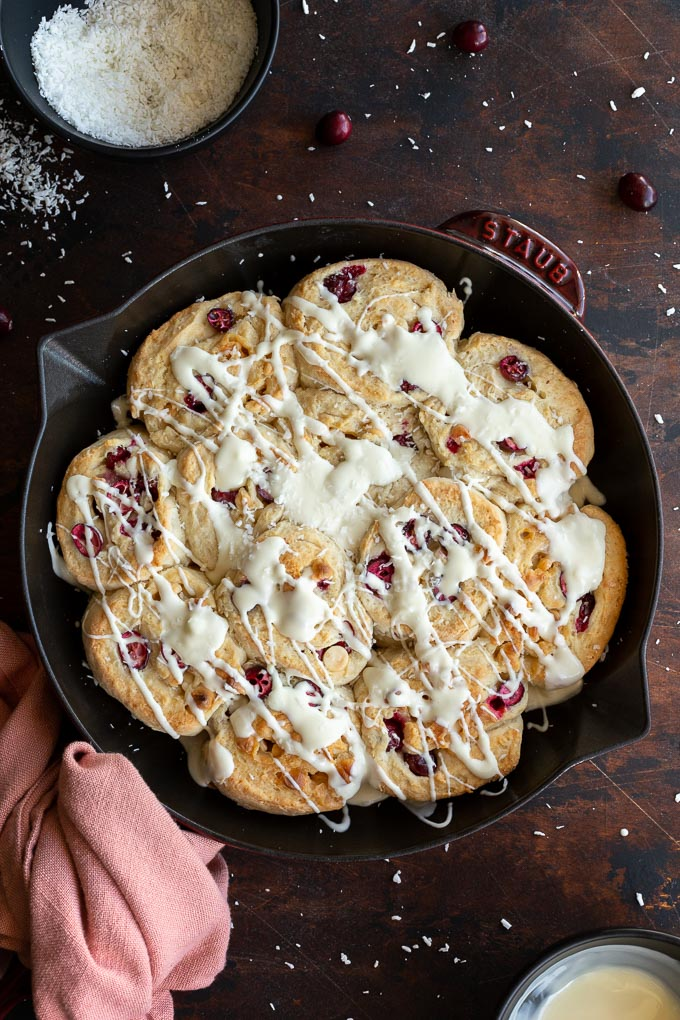 Overhead view of cranberry rolls topped with white chocolate in a cast iron skillet on a dark surface.