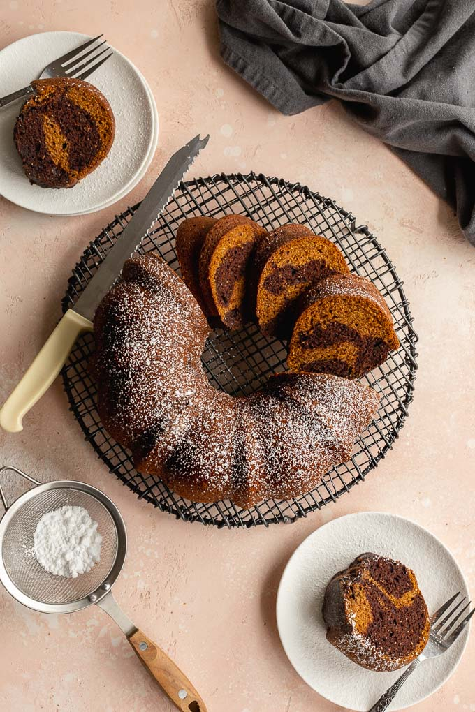 Overhead view of a pumpkin chocolate bundt cake on a wire rack and cut into some slices.