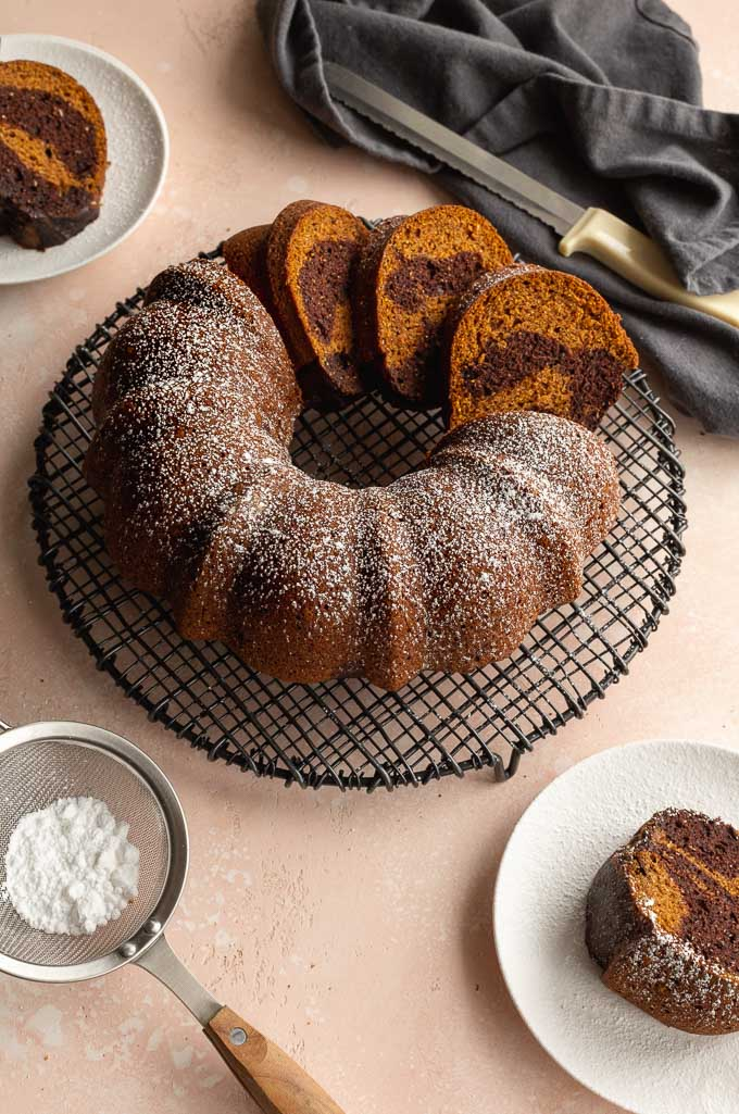 Pumpkin bundt cake on a wire rack and dusted with icing sugar.