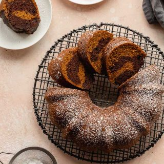 Pumpkin bundt cake on a round rack with a dusting of icing sugar on top.