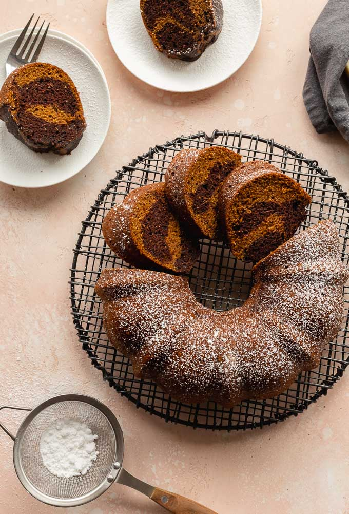 Pumpkin spice bundt cake on a cooling rack with a few slices cut out and placed on plates.