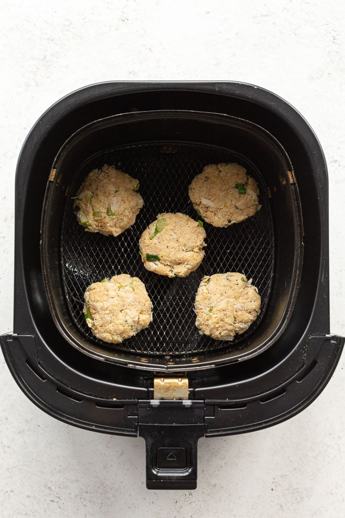 Overhead view of uncooked crab cakes in an air fryer basket.