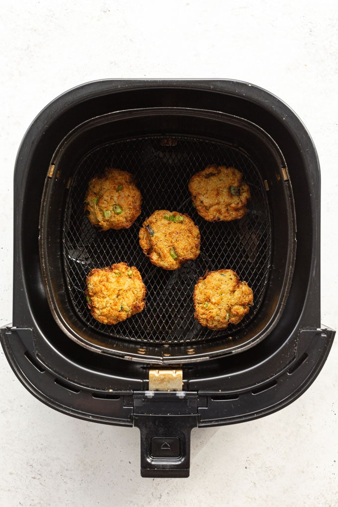 Overhead view of cooked crab cakes in an air fryer basket.