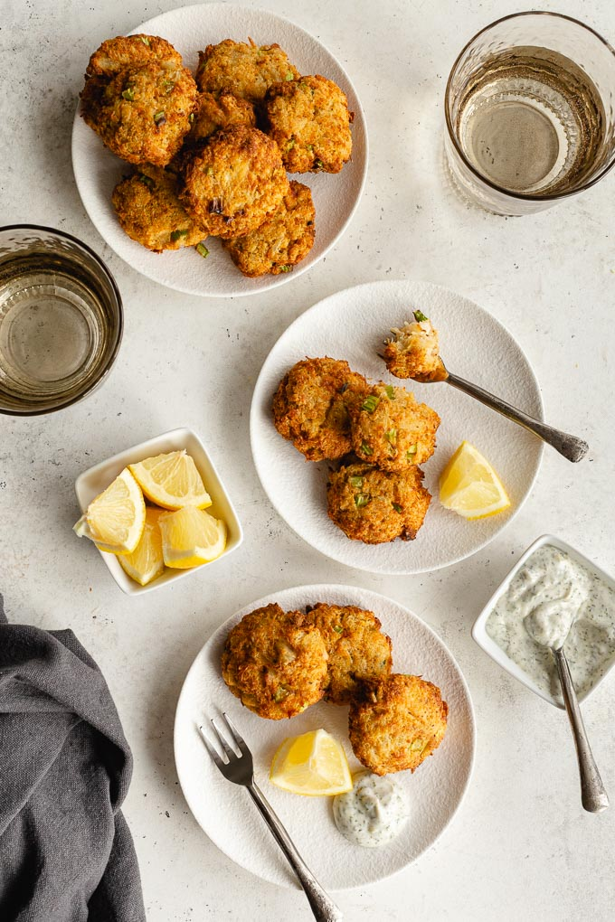 Crispy crab cakes arranged on three white plates with lemon wedges and herb dip.