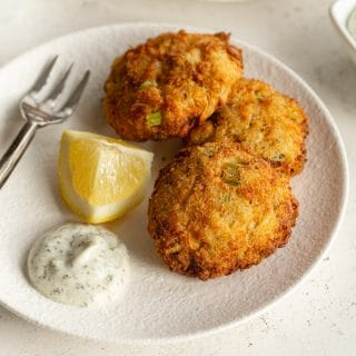 Three air fried crab cakes arranged on a white plate with herb dip and a lemon wedge.
