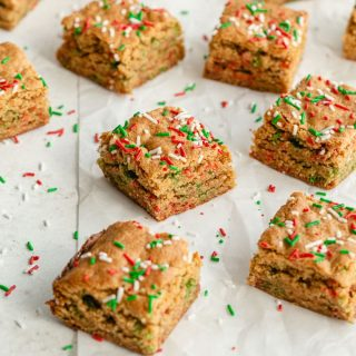 Christmas blondies cut into squares and arranged on a sheet of parchment paper.