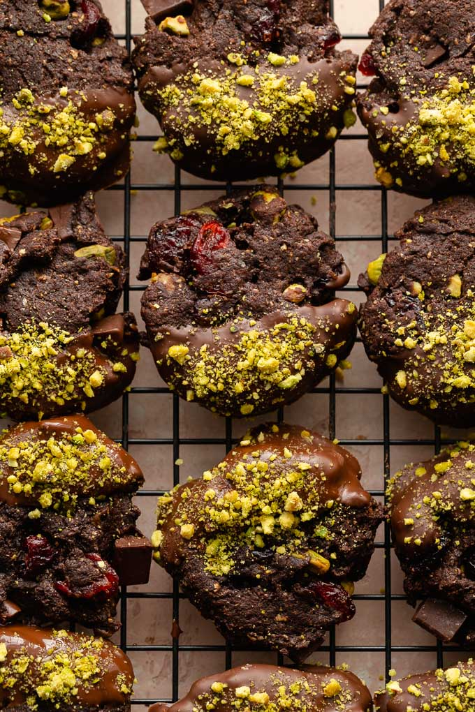 Up-close and overhead view of chocolate dipped pistachio cranberry cookies.