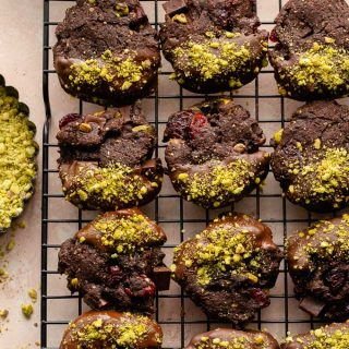 Chocolate dipped cranberry pistachio cookies arranged on a wire rack.
