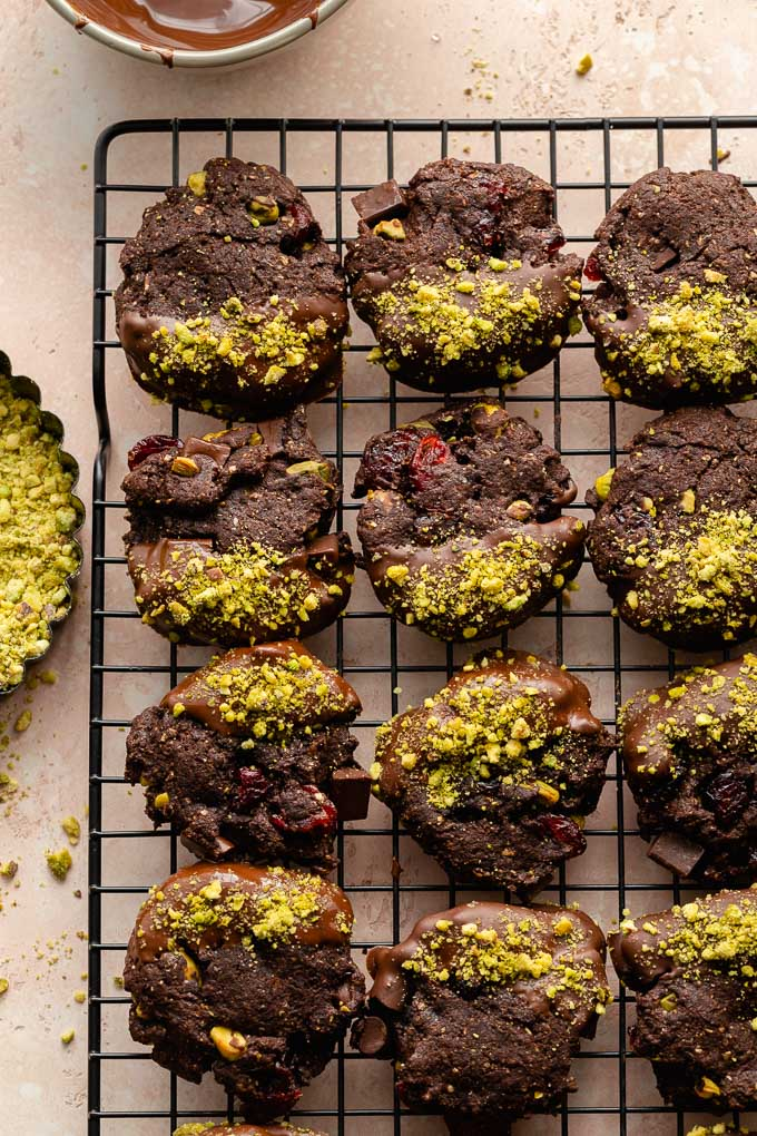 Cranberry pistachio cookies dipped in chocolate and arranged on a cooling rack.