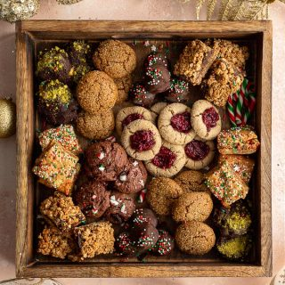 Assorted dairy-free cookies arranged in a holiday cookie box.