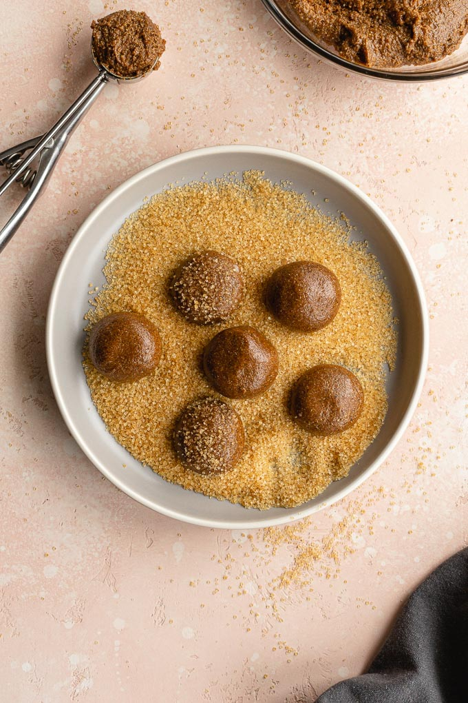 Cookie dough balls on a plate and being rolled in sugar.
