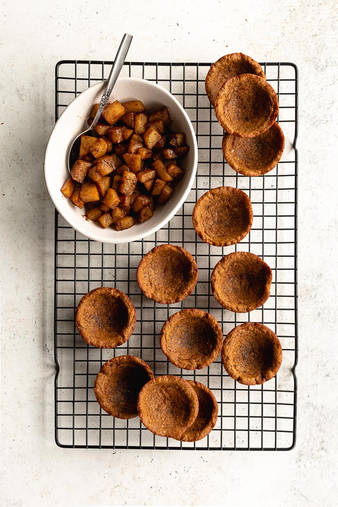 Cookie cups arranged on a black wire rack next to a bowl of sautéed pears.