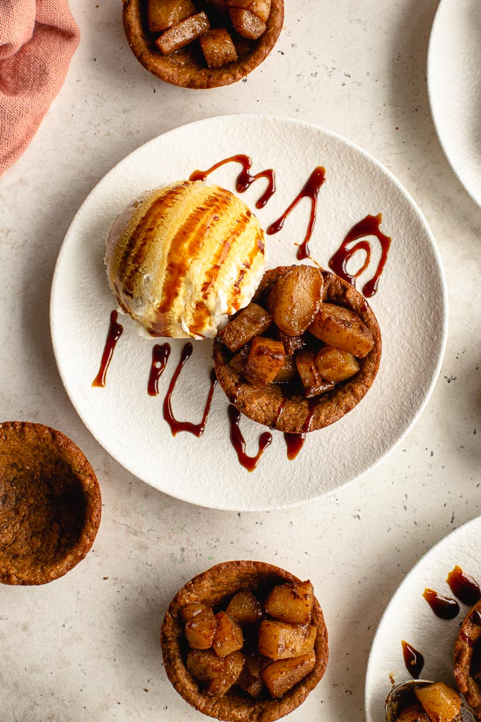 Up close view of a gingerbread cookie cup on a white plate with spiced pears and a scoop of ice cream.