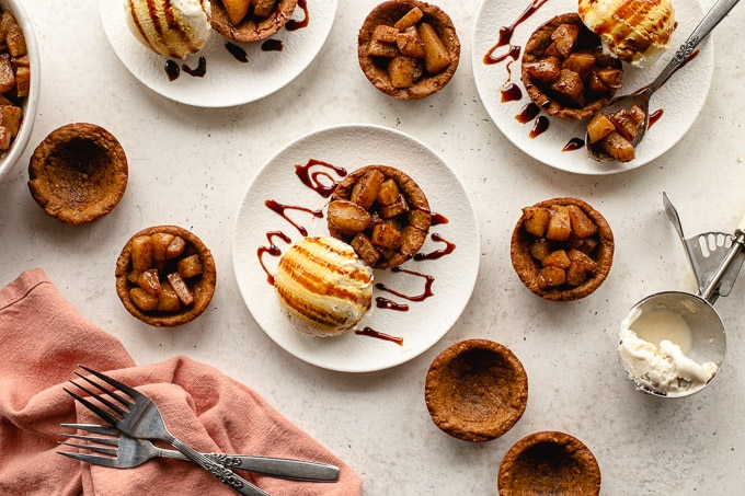 Gingerbread cups arranged on plates and filled with spiced pears.