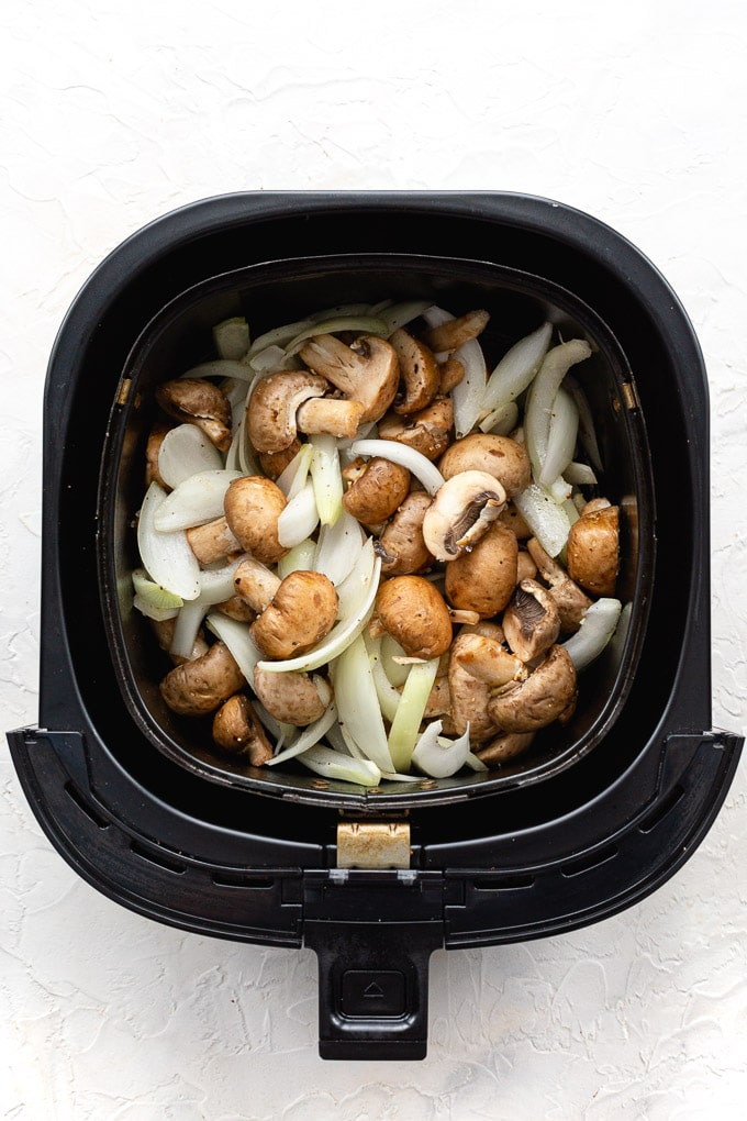 Overhead view of raw sliced onions and mushrooms in an air fryer basket.