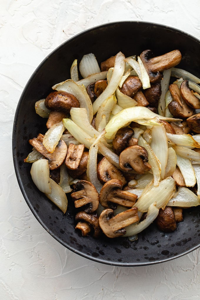 Up close view of air fryer mushrooms and onions in a black bowl on a white surface.