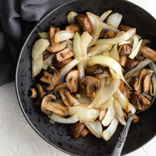 Air Fryer Mushrooms and Onions served in a black bowl on a white backdrop.