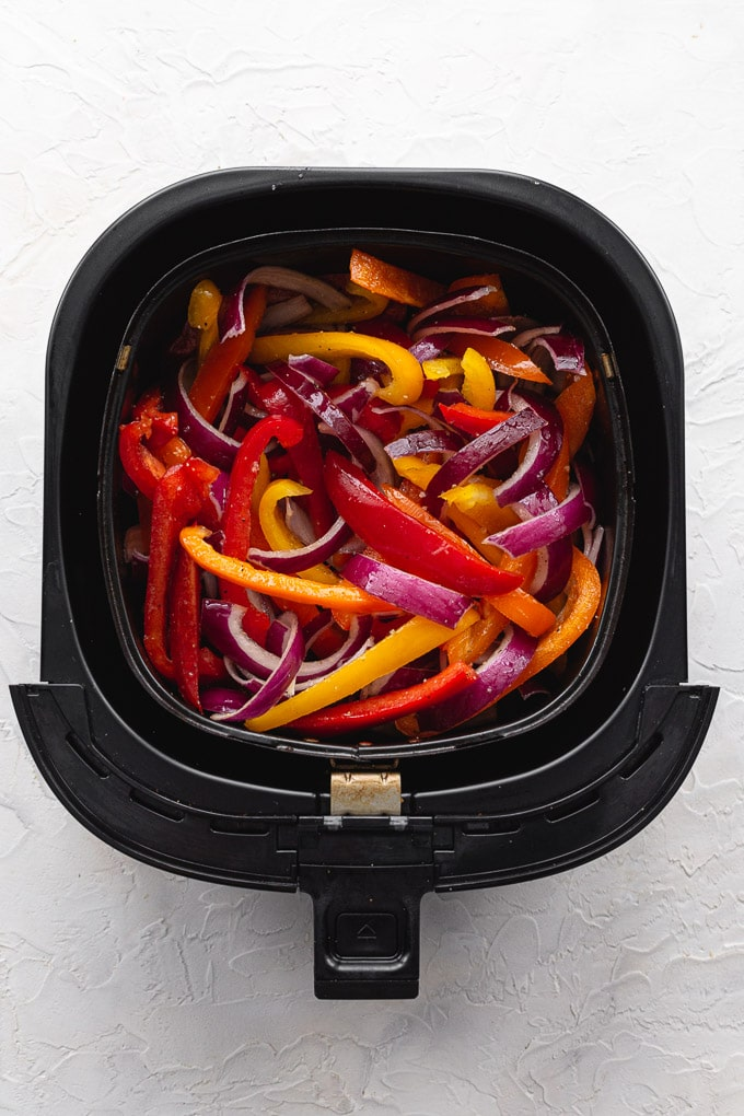 Raw slices of seasoned onions and peppers in an air fryer basket.