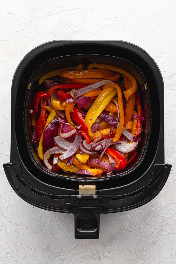 Overhead view of air fried slices of peppers and onions in an air fryer basket.