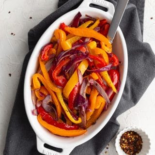 Overhead view of Air Fryer Peppers and Onions served in a white oval dish with a spoon inserted into it.