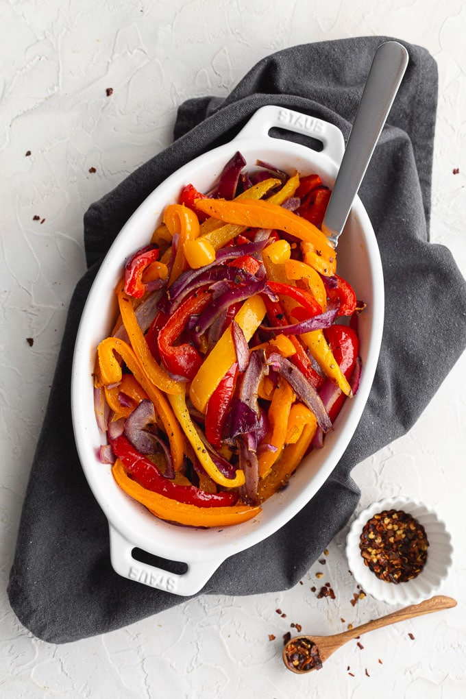 Air fried peppers and onions served in a white oval dish on a grey napkin.
