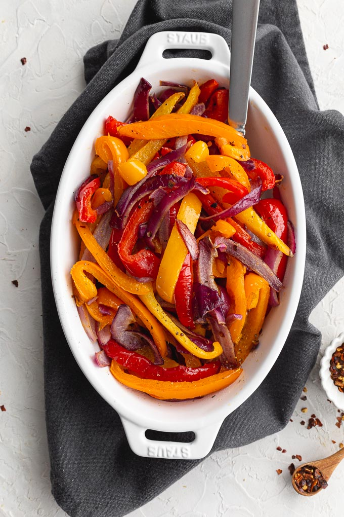 Overhead view of air fryer bell peppers and red onions in an oval dish on a grey cloth.