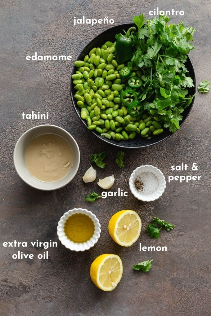 Ingredients to make this edamame hummus recipe arranged individually and labelled.