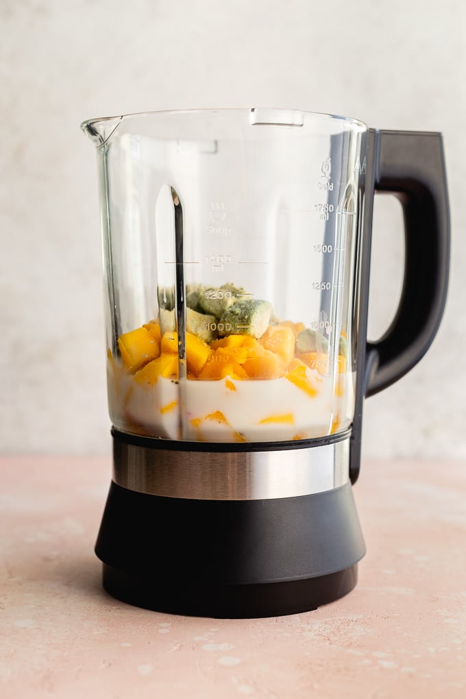 Side view of a blender jar with all of the smoothie ingredients layered on top of each other.