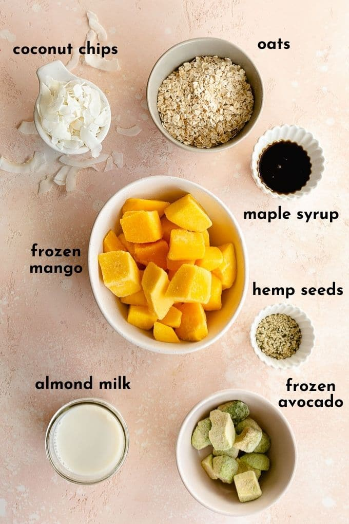 Ingredients to make a mango smoothie with oats arranged individually and labelled.
