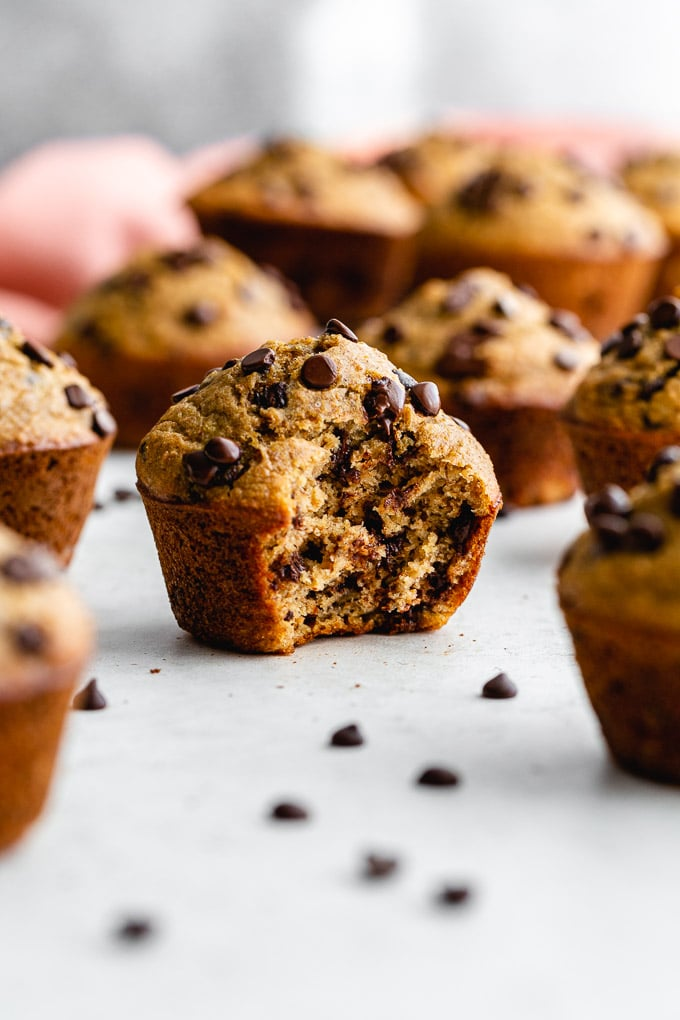 Side view of a chocolate chip banana spelt muffin with a bite taken out of it.