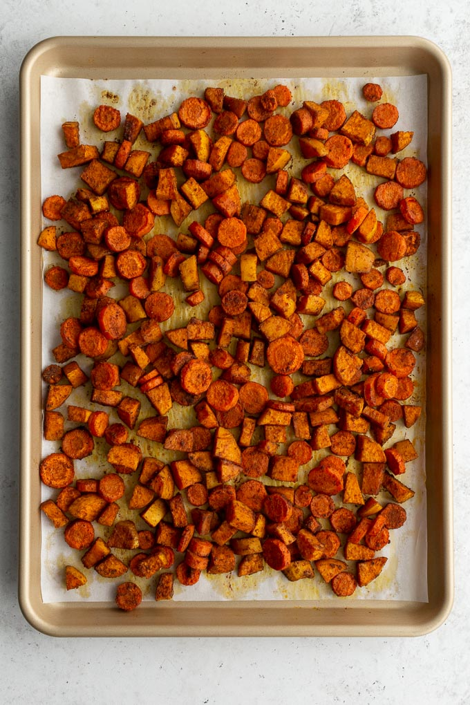 Chopped and roasted sweet potatoes and carrots on a sheet pan.