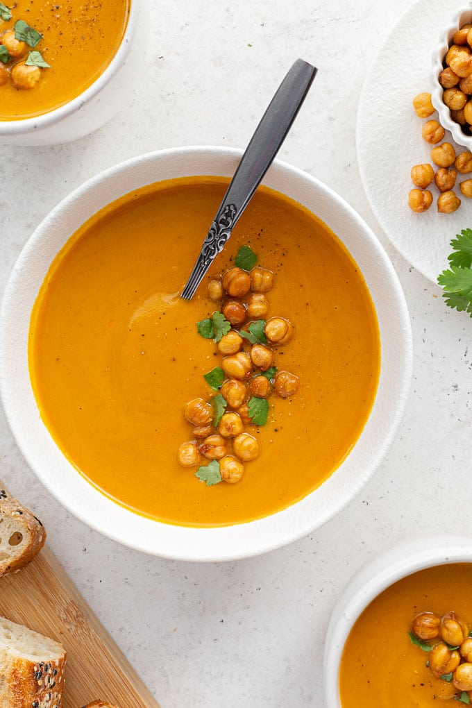 Overhead view of sweet potato and carrot soup in a white bowl with a spoon inserted into it.
