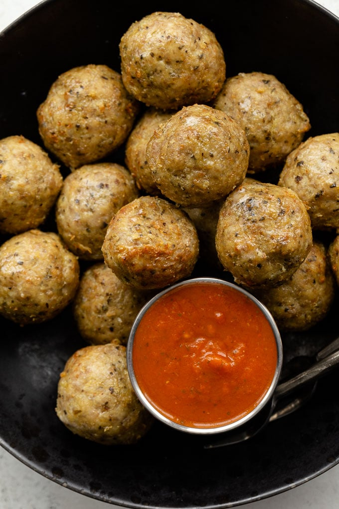 Up close view of chicken meatballs in a bowl and served with marinara sauce on the side.