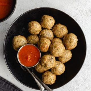 Air fryer chicken meatballs served in a black bowl with forks and marinara sauce on the side.