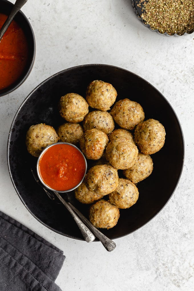 Overhead view of air fryer chicken meatballs arranged in a black bowl with marinara on the side.