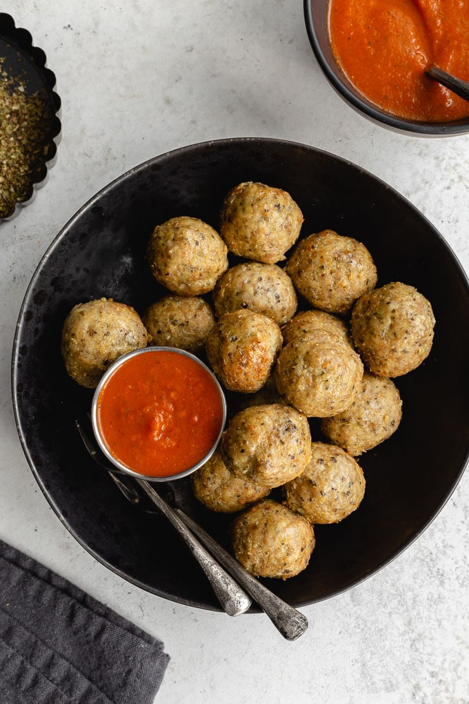 Chicken meatballs served in a black bowl with homemade marinara sauce on the side.